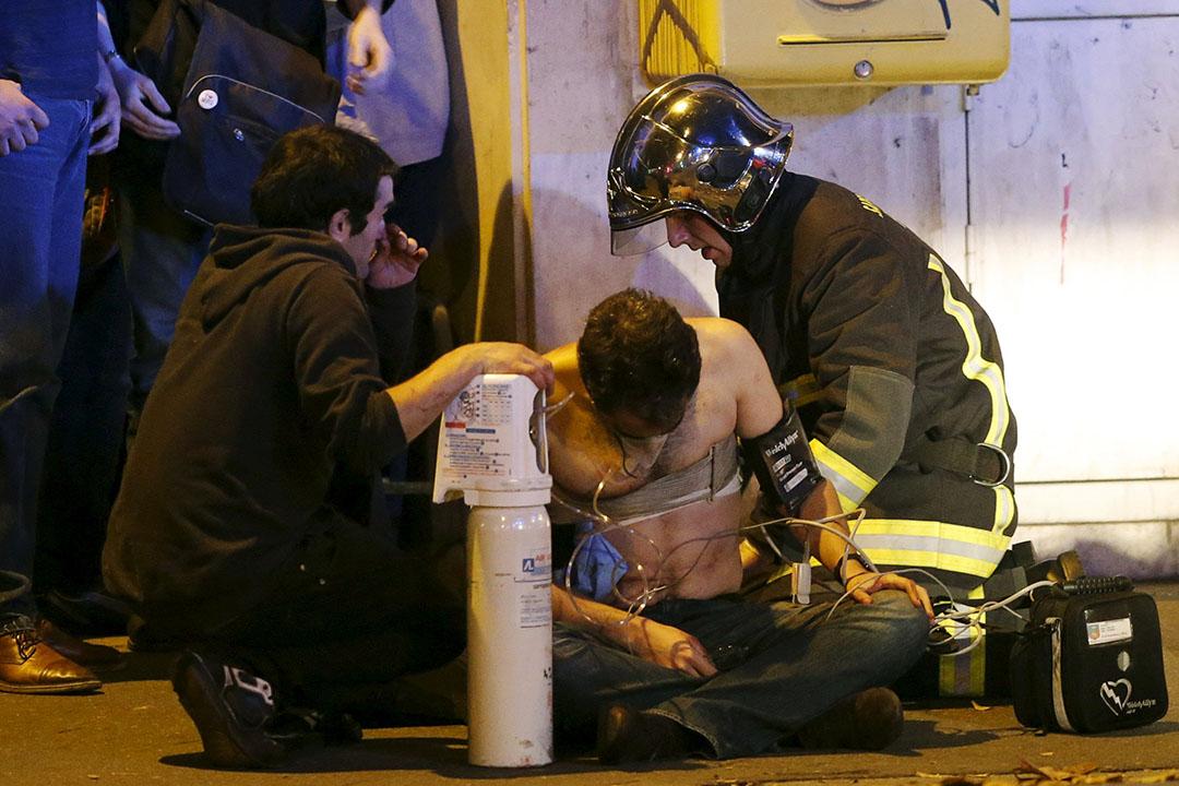 Bataclan音樂廳外,一名受傷男子正接受消防員急救。攝:Christian Hartmann/REUTERS
