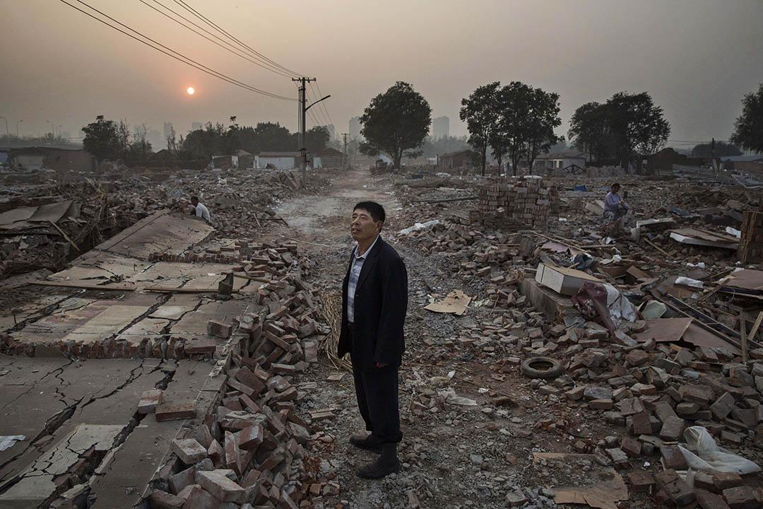 2015年10月16日,北京,通州區故城,一名村民站在被拆卸的村落瓦礫之中。該村因北京城市化而被拆卸。攝:Kevin Frayer/GETTY