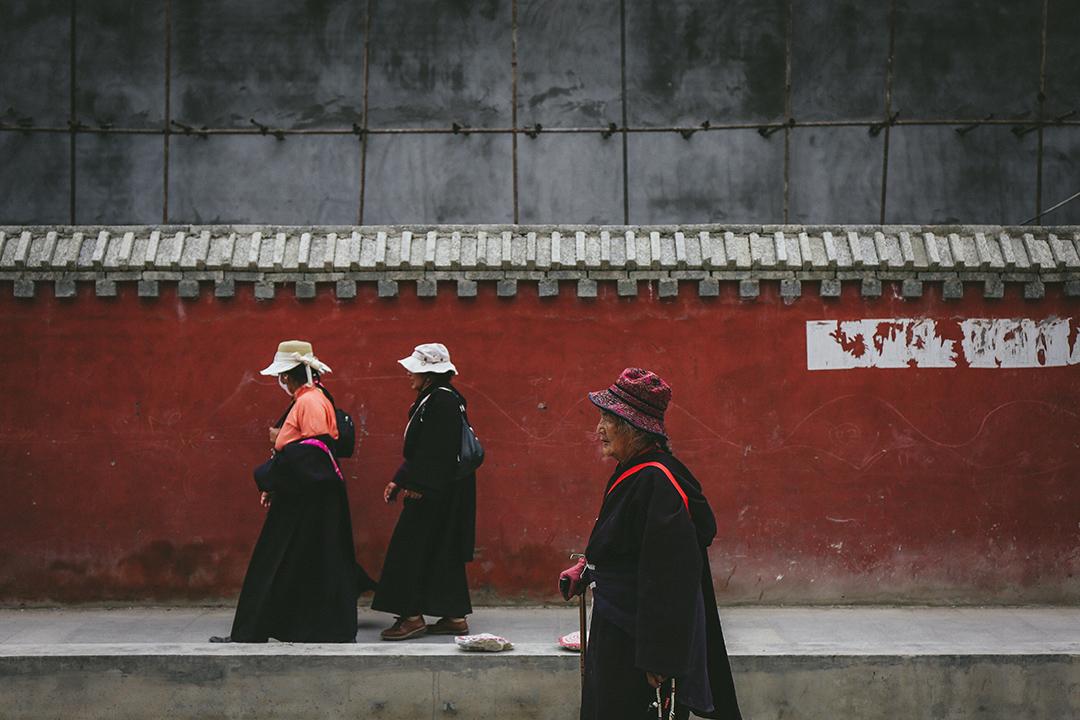 幾位藏族群眾從新寨嘉那嘛呢石堆附近走過。攝 : 王嘉豪/端傳媒