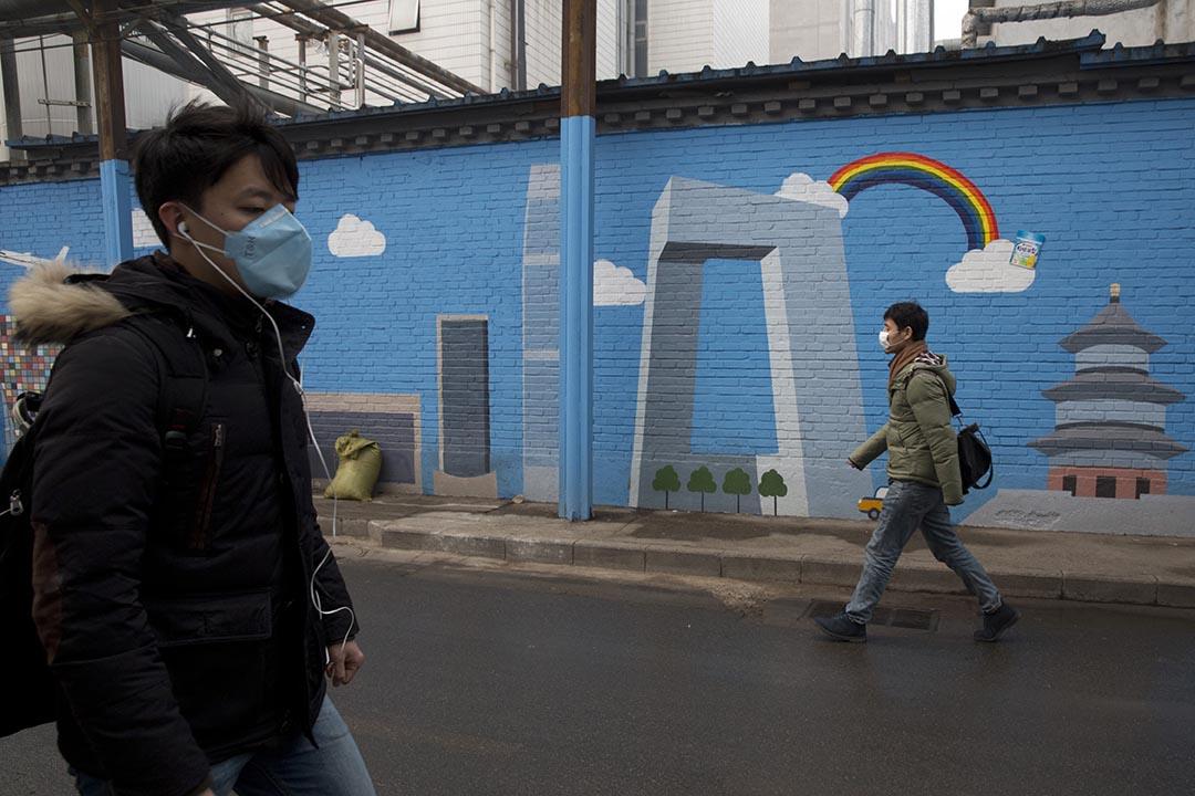 北京於12月18日啟動了本月第二次空氣重污染紅色預警,圖為北京市民在一幅藍天白雲的壁畫前走過。攝:Ng Han Guan/AP