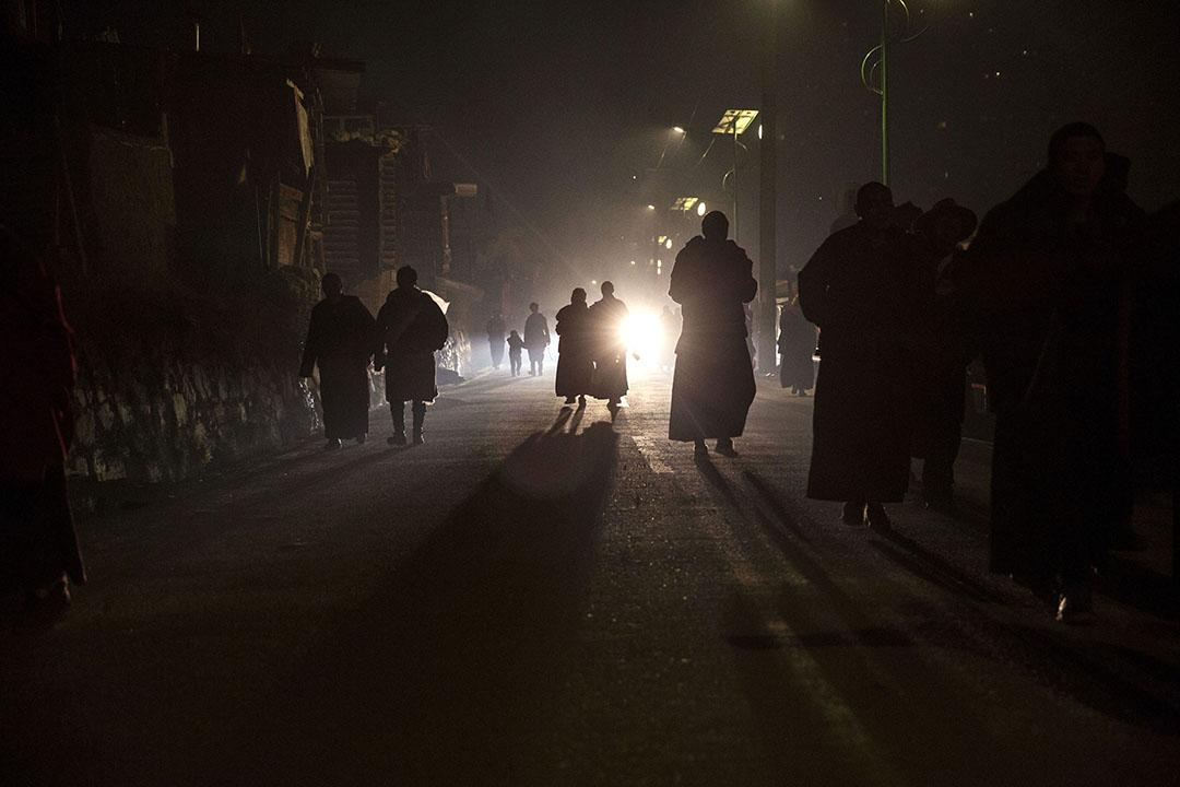 喇嘛們晚上離開佛學院,沿著黑暗的路回家。攝:Kevin Frayer/Getty Images