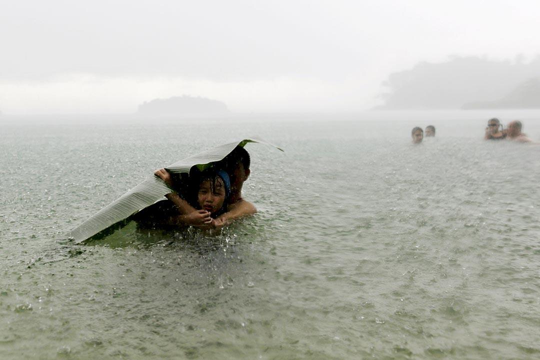 2015年10月17日,在巴拿馬科隆市郊區,一名女孩用蕉葉抵擋暴雨。攝:CARLOS JASSO/Reuters