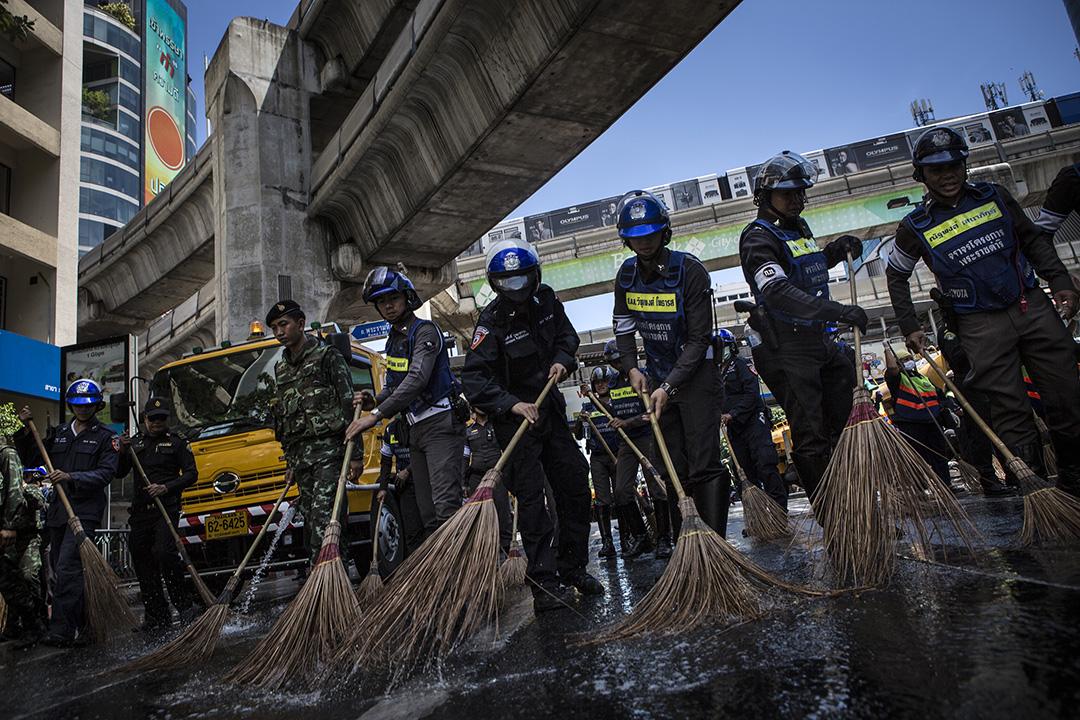 警察與軍人合力清理爆炸現場附近路面。