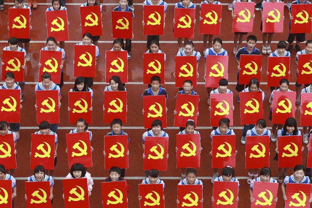 2015年10月10日,北京大學主辦了首屆「世界馬克思主義大會」。圖為一群小學生手持共產黨黨徽拍照。 攝:China Daily/REUTERS