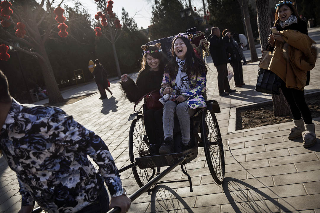 2015年2月25日,北京,兩名少女在農曆新年的廟會上坐人力車。攝:Kevin Frayer/GETTY
