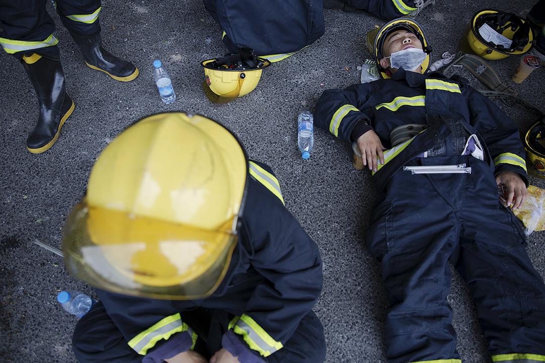 消防員經過連夜救災,躺在地上休息。