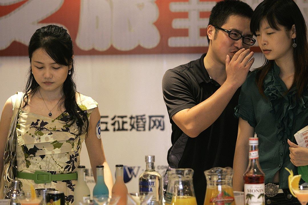 多項科學研究指出,人類愛講八卦並非壞事。圖為一對參男女在輕聲交談。攝:China Photos/GETTY
