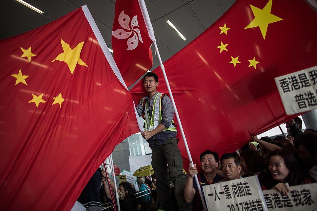 《行政長官普選辦法公眾諮詢報告及方案》4月22日在立法會公布,其間支持政改的示威者於立法會門外揮動中國國旗和特區區旗。攝:Lam Yik Fei/GETTY