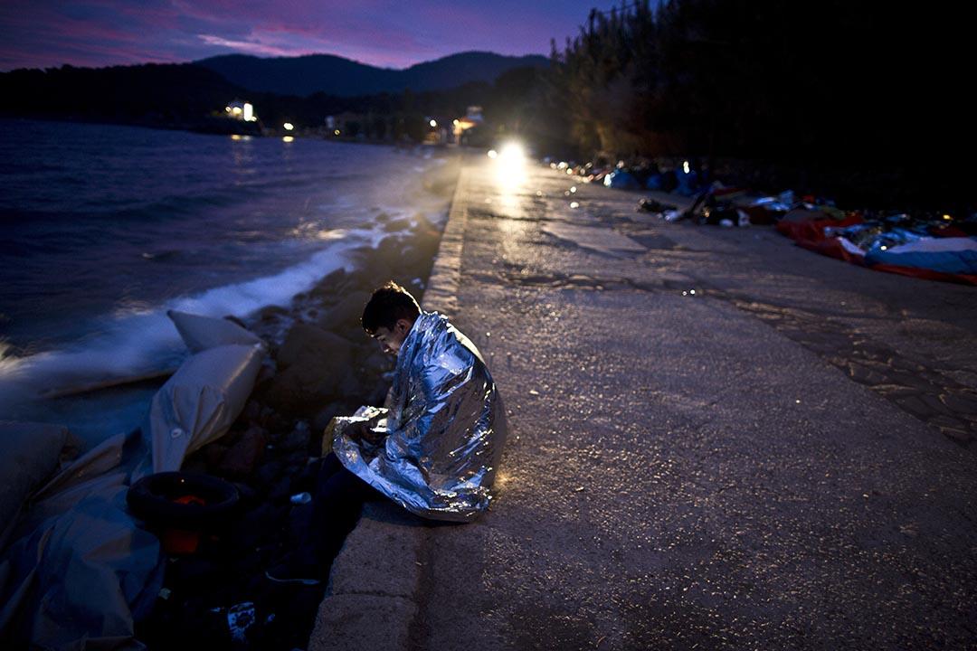 2015年10月8日 土耳其海岸萊斯沃斯島 一名阿富汗難民包裹毛毯坐在海旁休息,等待機會前往歐盟國家。攝 : Muhammed Muheisen/ AP