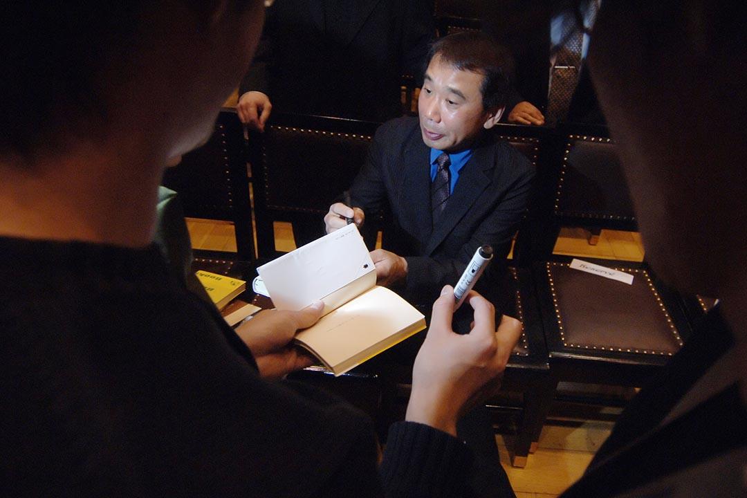 2006年10月30日,村上春樹在捷克布拉格獲得卡夫卡文學獎後,為在場人士簽名。攝:MICHAL CIZEK/AFP