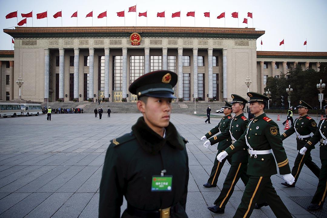 2016年3月5日,中國北京,解放軍士兵在人民大會堂前走過。攝:Damir Sagolj/REUTERS
