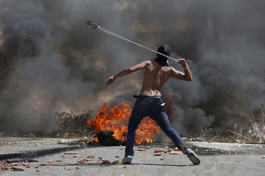 2015年10月5日,約旦河西岸 一名巴勒斯坦示威者使用彈弓向以列色保安部隊彈射石頭。攝:Mohamad Torokman/ REUTERS