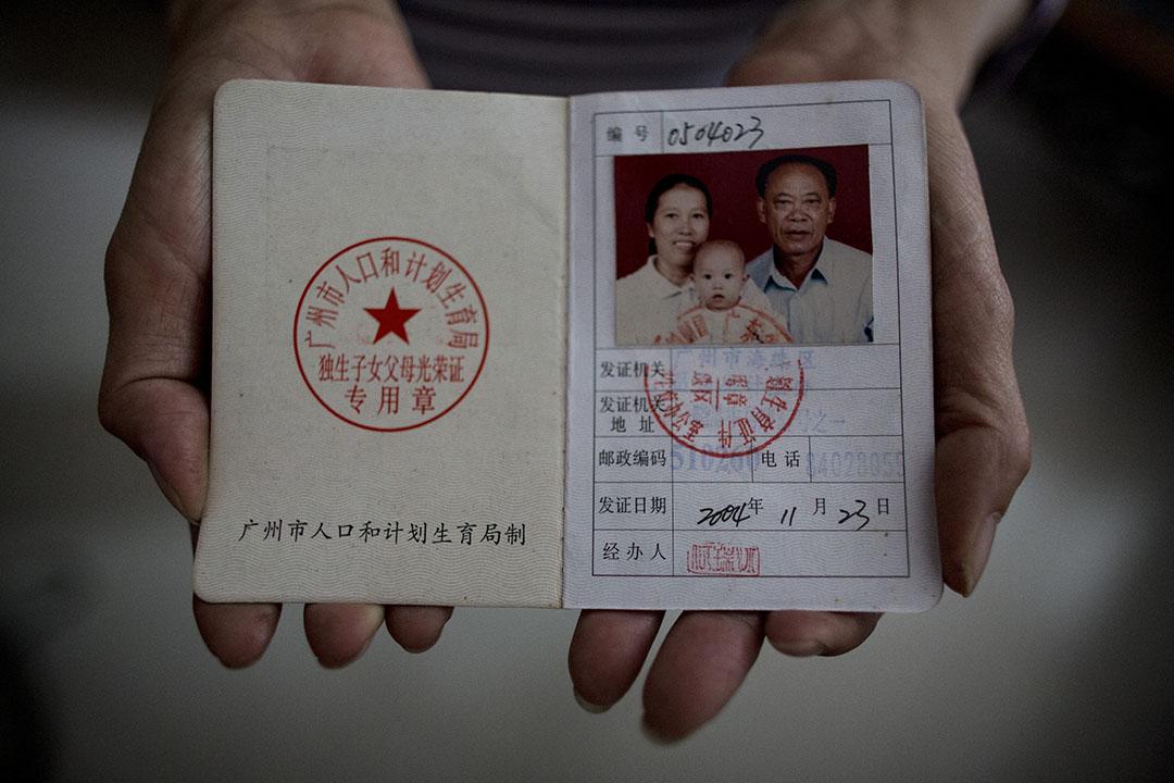 中共中央五中全會決議中止推行了36年的一胎化政策。圖為廣州一名失獨家長拿着獨生子女父母光榮證,攝:林亦非/端傳媒