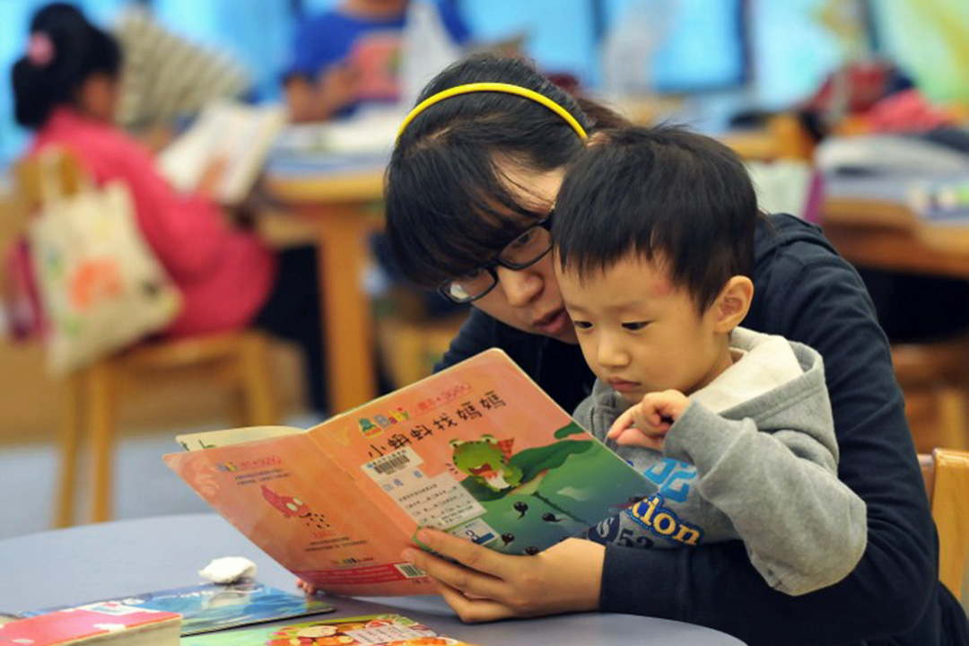 圖為一名母親與孩子在台北國立圖書館閱讀圖書。攝:Mandy Cheng/AFP