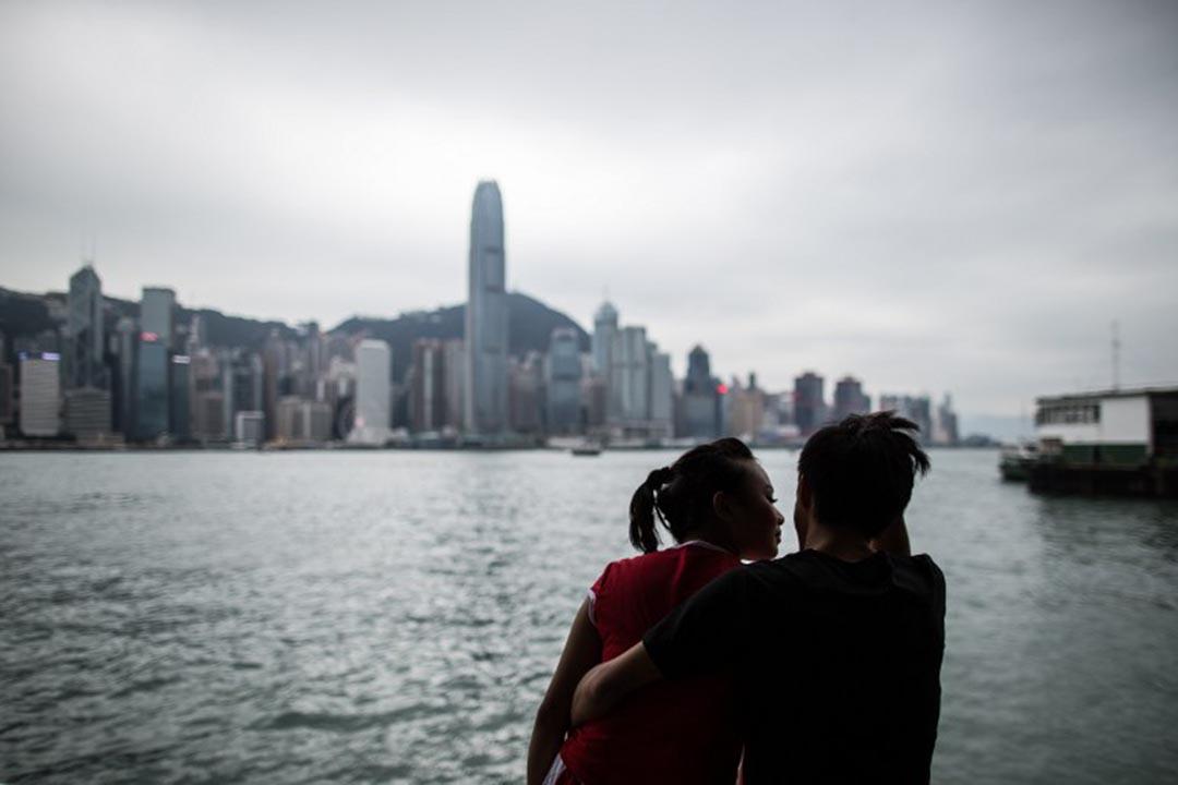 一對情侶在尖沙咀海旁談情。攝:ANTHONY WALLACE/AFP