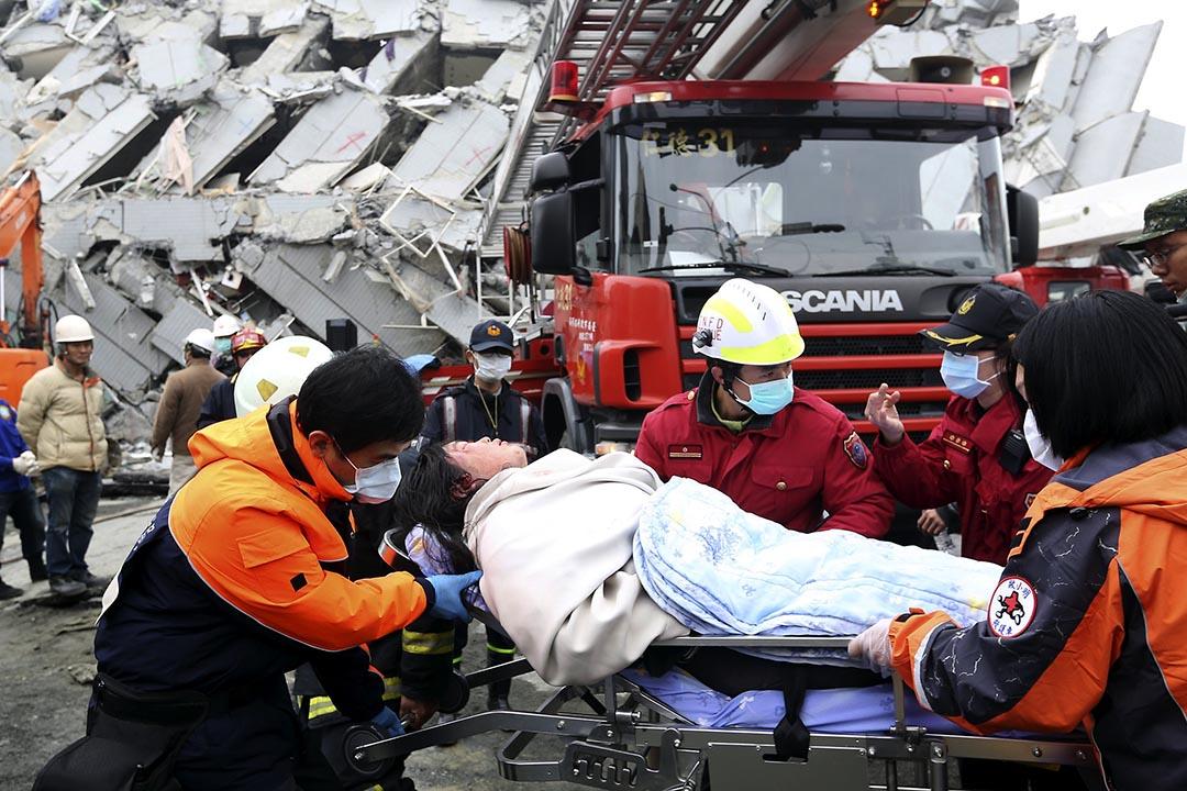 救援人員在台南永大台一棟倒塌的樓房內運送傷者離開現場。攝 : Patrick Lin/REUTERS