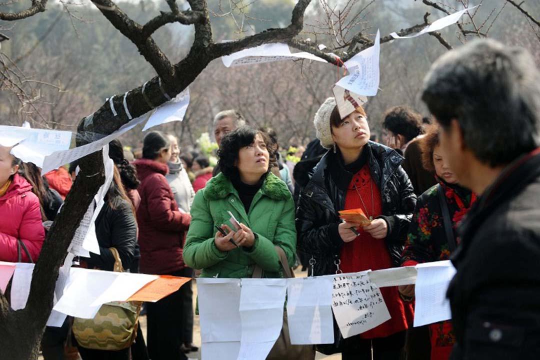 湖北省武汉市,單身青年和家長在公園觀看相親信息。攝:MIAO JIAN / IMAGINECHINA