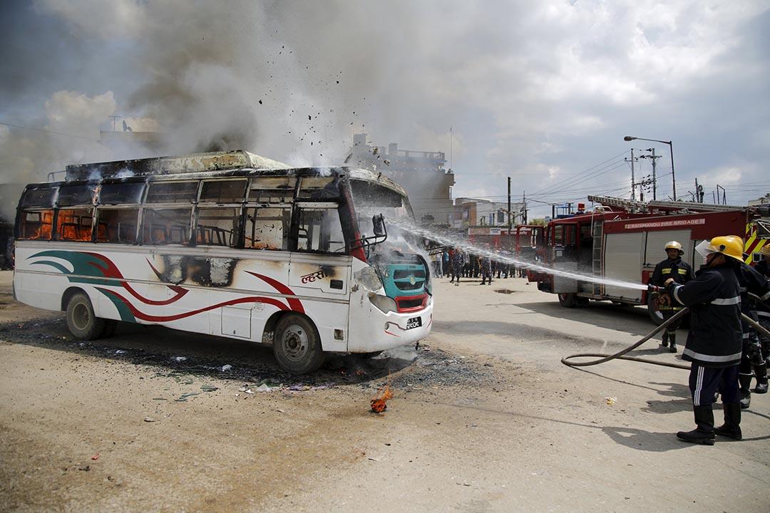 2015年9月20日,尼泊爾加德滿都一輛巴士在全國大罷工期間被放火燒毀,消防員正在撲救。攝 : Navesh Chitrakar/REUTERS