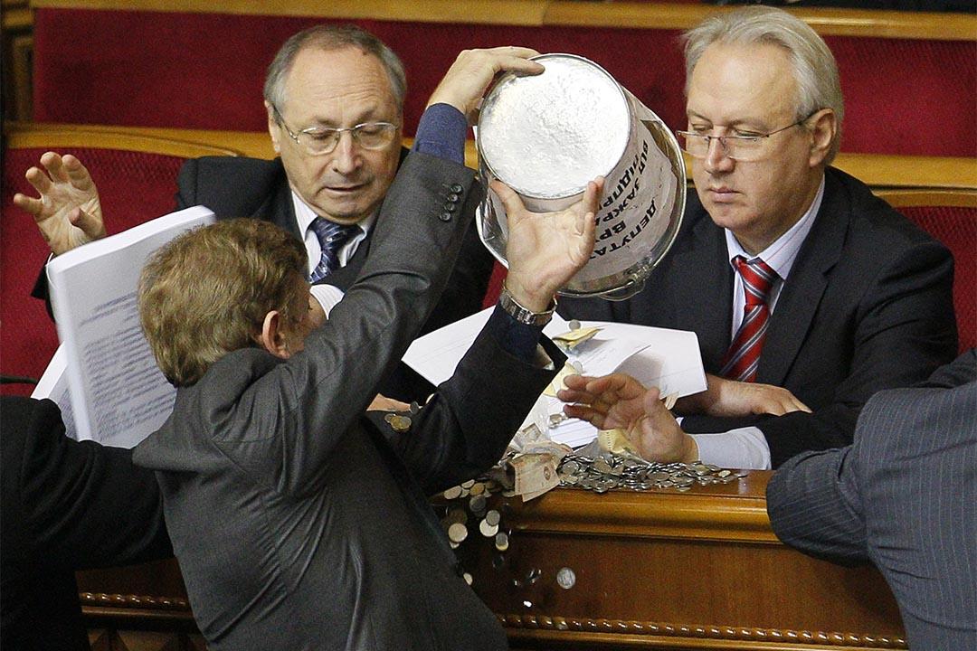 烏克蘭議員將一桶錢幣倒向一名政府官員。攝:Sergey Svetlitsky/REUTERS