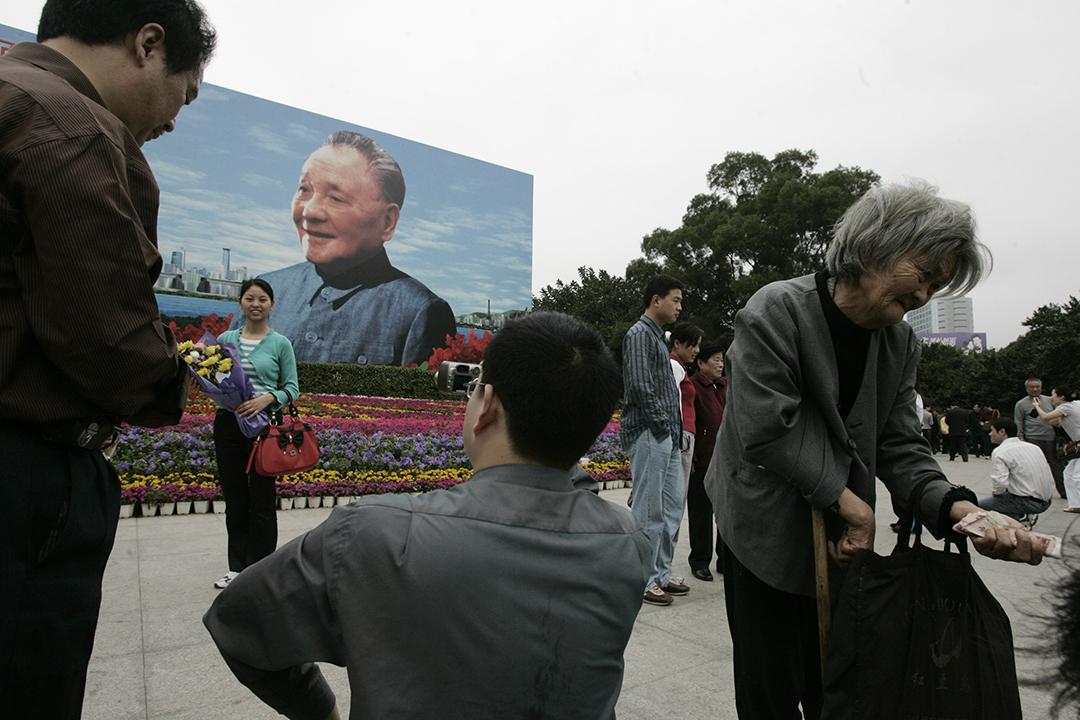 一名婦人在深圳鄧小平畫像前行乞。攝:Paul Yeung/REUTERS