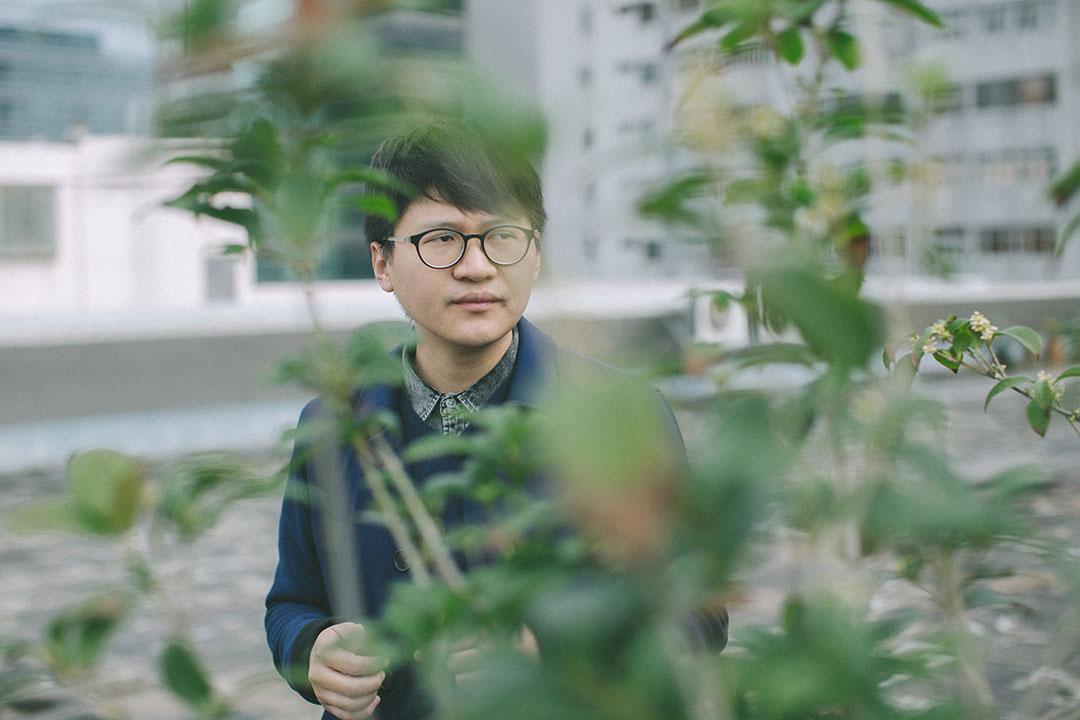 Trevor Yeung 在刺點畫廊的天台。他面前的桂花樹,是他去年在香港巴塞爾藝術展上個人展《遊園:不太容易做綠色》中使用的創作材料。攝:王嘉豪/端傳媒