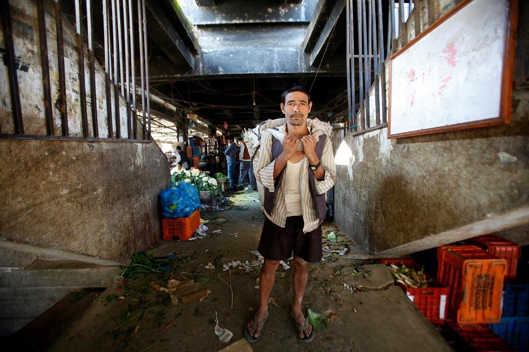 54歲的搬運工Krishna Bhujel在加德滿都某蔬菜市場等待工作,他手中拿着一個空編織袋(Doko)。攝 : Bikram Rai