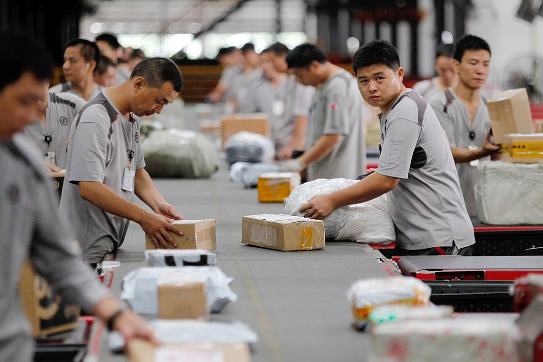 2014年中國大陸人均發送快遞已達10.2件。圖為中國工人在深圳市的一個轉運中心排序包裹。攝: Zhu linxiao/Imaginechina
