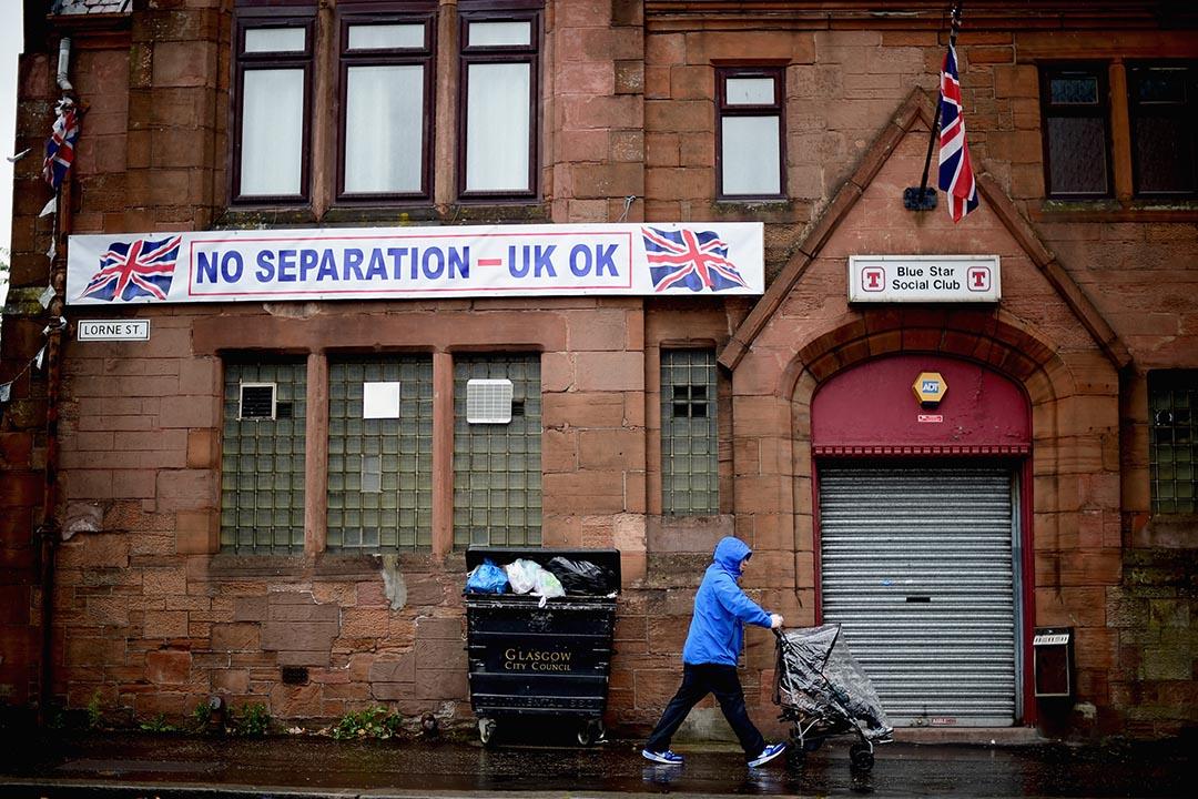 一名市民在貼有支持統一派標語的社交俱樂部外走過。攝 : Jeff J Mitchell/GETTY