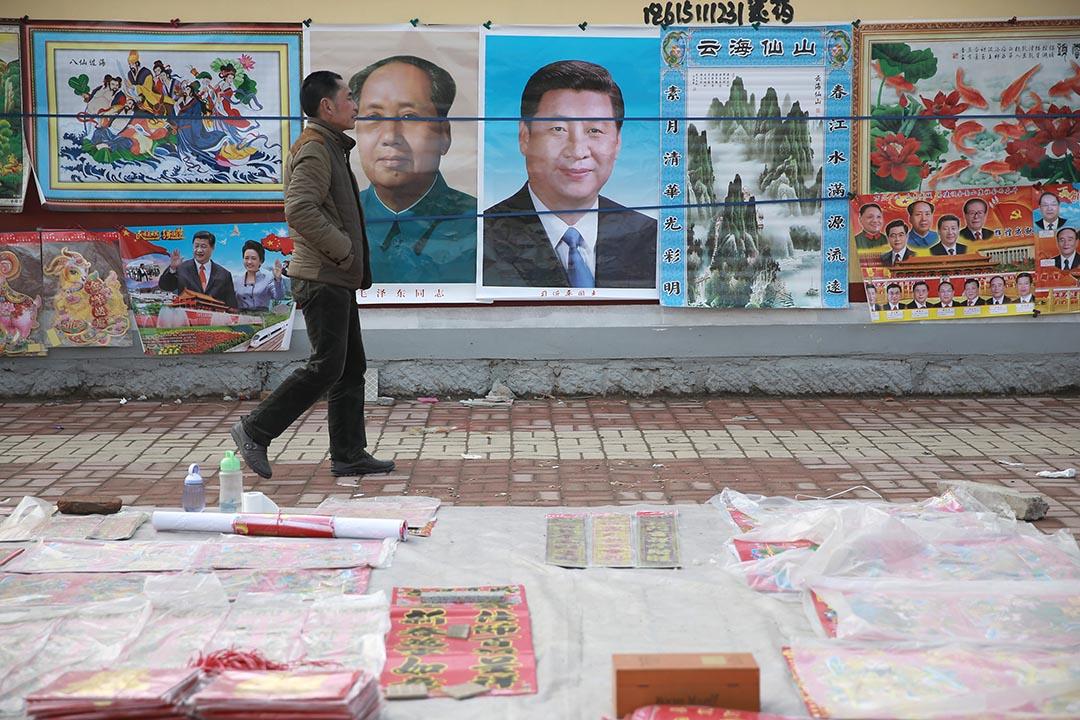 一名男子在中國國家主席習近平和中國的主席已故毛澤東畫像前走過。REUTERS