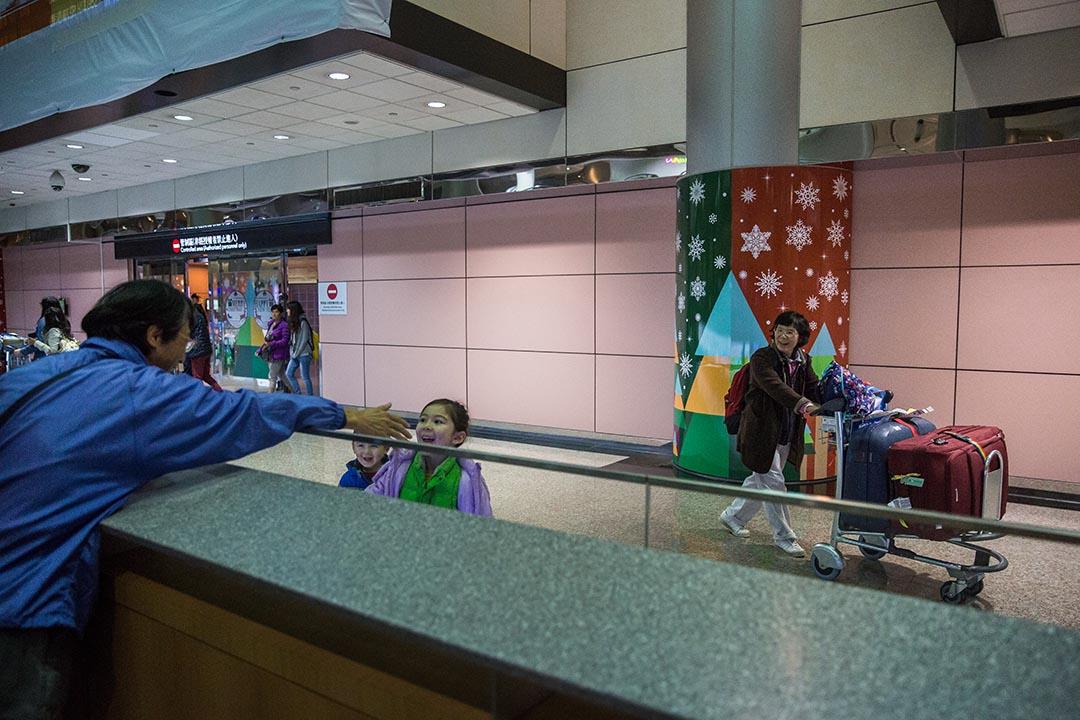王進榮於接機大廳等待妻子通關。攝:Billy H.C. Kwok/端傳媒