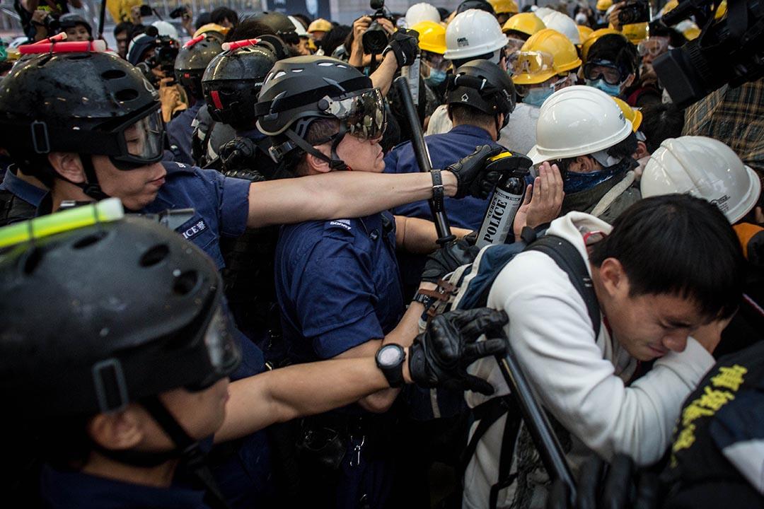 去年雨傘運動期間警方驅散在政府總部附近的示威者,有警員向示威者舉起胡椒噴霧。 攝:Chris McGrath/Getty