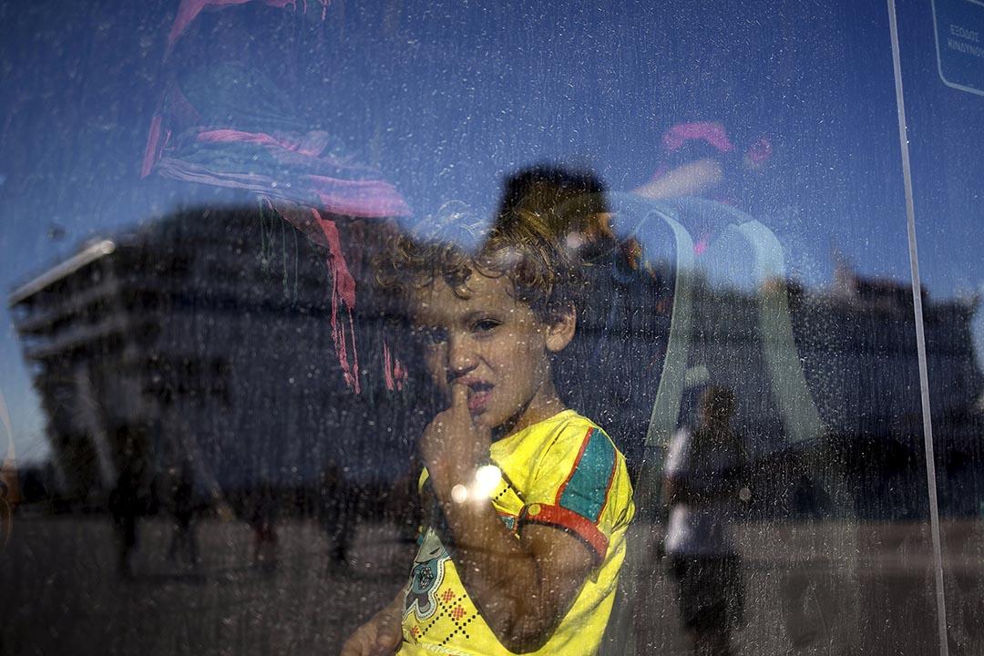 2015年8月25日 運載難民的郵輪反射在一名難民兒童乘坐的巴士車窗上。攝: Stoyan Nenov /REUTERS