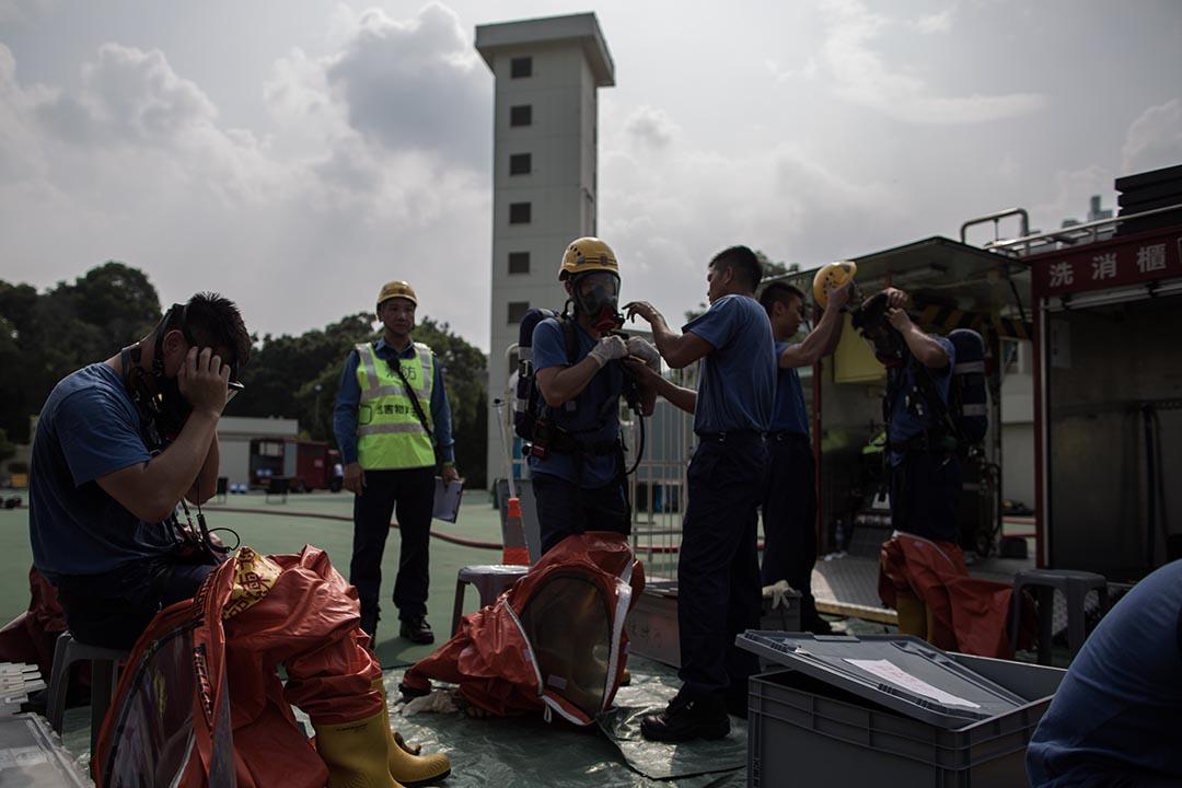 消防人員配戴裝備及穿上化學保護袍準備進行危害物質洩漏事故演習。攝:盧翊銘/端傳媒