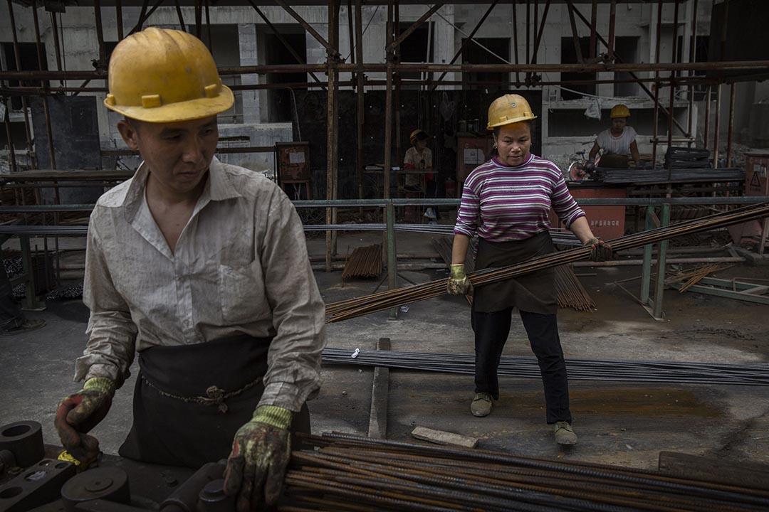 2014年8月29日,北京,一名女地盤工人與男工友在地盤內工作。攝:Kevin Frayer/GETTY