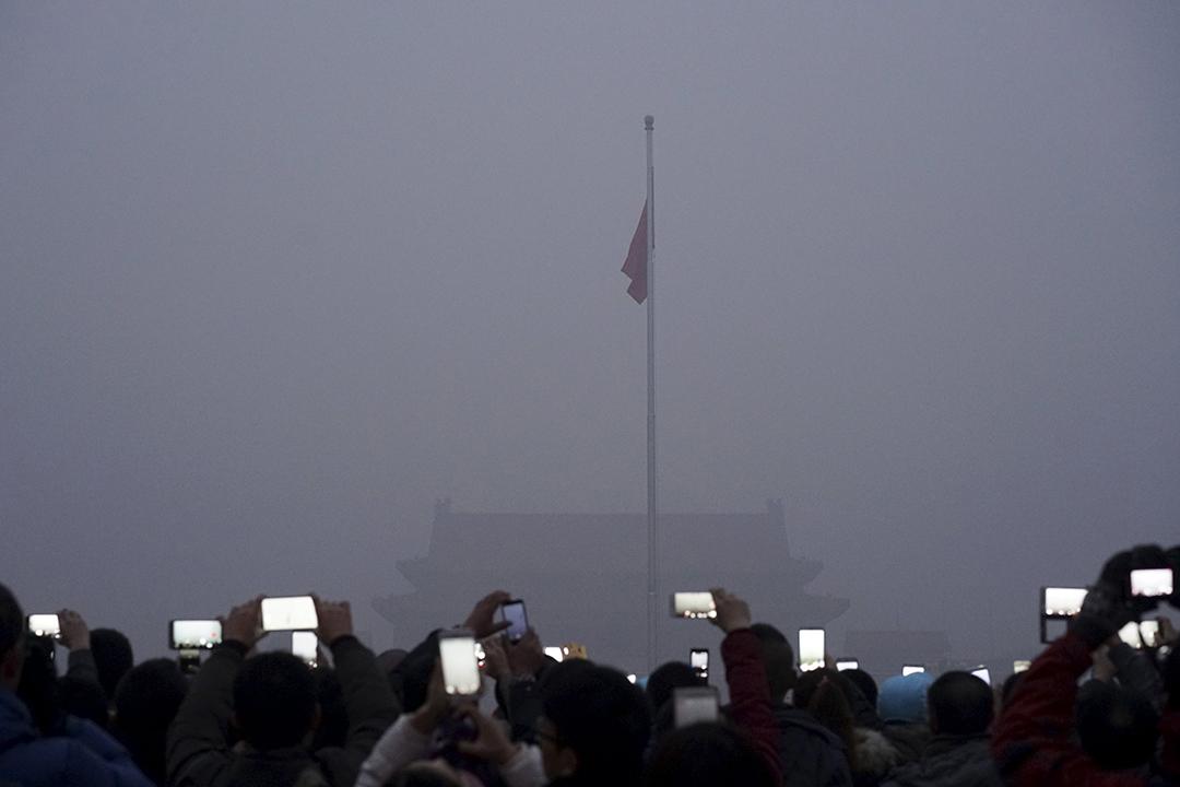 天安門廣場清晨的升旗禮,霧霾下只見手機發出的光芒。攝:REUTERS