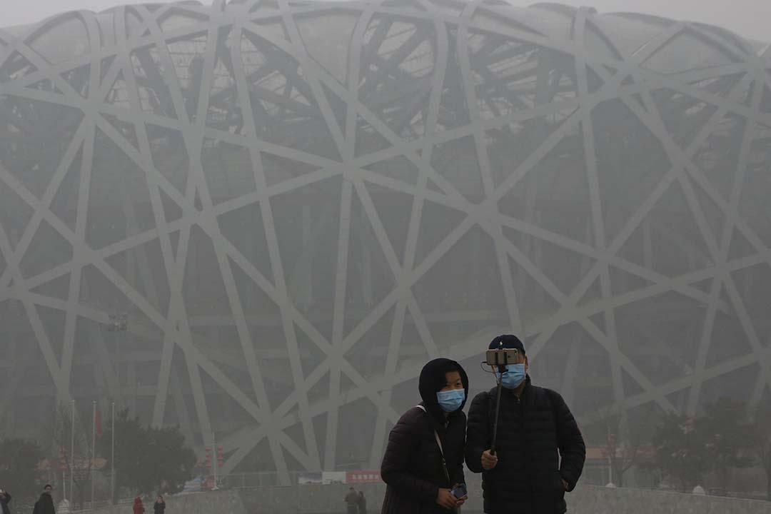 旅客在霧霾籠罩下在鳥巢體育館前合照。攝:Kim Kyung-Hoon/REUTERS