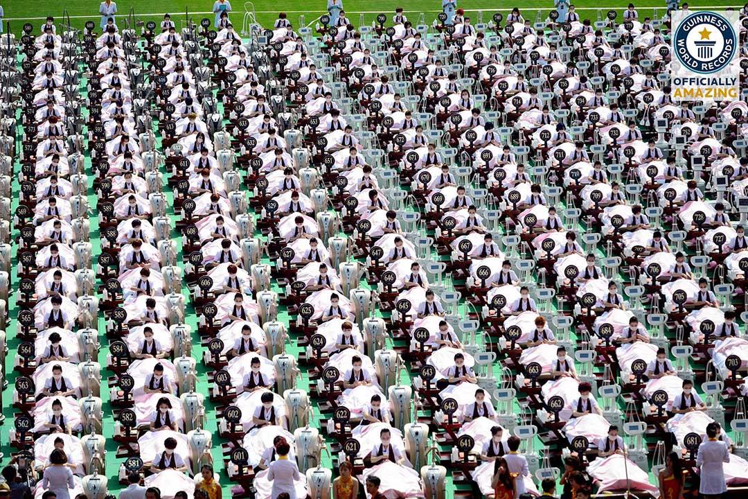 """2015年5月4日,山東省體育中心體育場上擺放了1000張美容床、1000個美容儀器,由1000名美容師為1000位愛美女士現場免費做面部護理,女士全部現場更衣穿上粉色浴袍,創造""""最多人接受面部護理""""的吉尼斯世界紀錄。Guinness World Record Facebook截圖"""