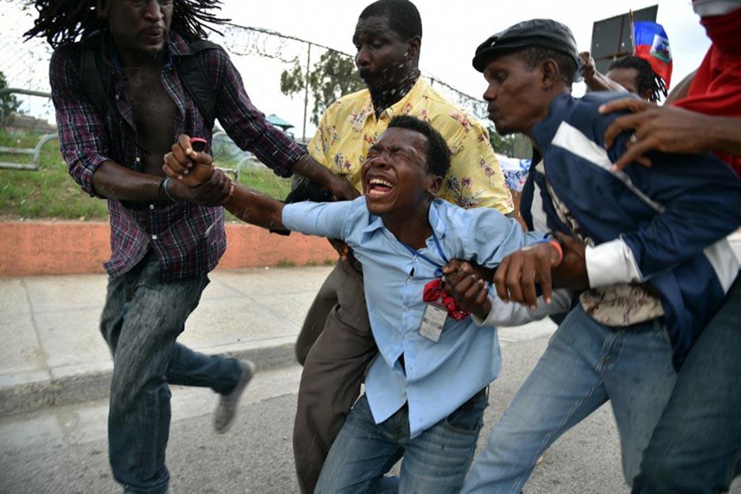 2015年12月16日,海地,一名記者被示威者襲擊,示威者因不滿海地臨時選舉委員會早前宣布首輪總統選舉最終結果而引發遊行。攝:HECTOR RETAMAL / AFP