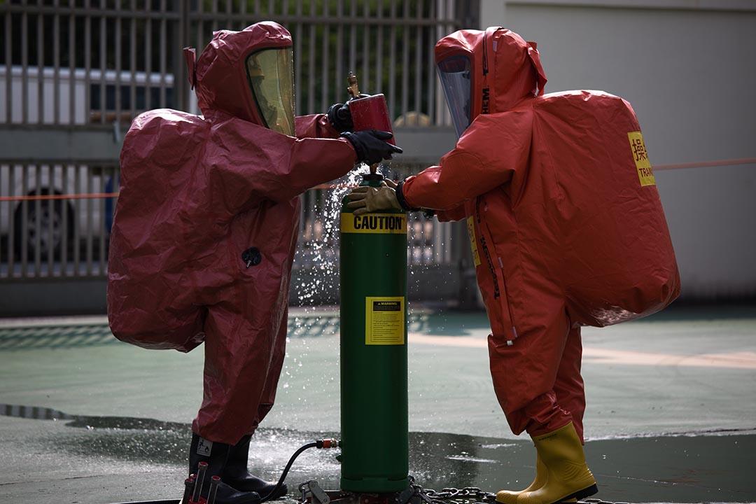兩名穿著 EVO 化學保護袍的消防人員正在進行模擬處理氯氣洩漏事故的工作。攝:盧翊銘/端傳媒