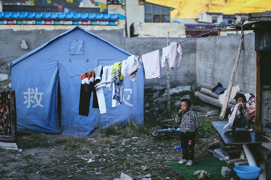 移民村內仍擺放了救灾用的帐篷。攝 : 王嘉豪/端傳媒