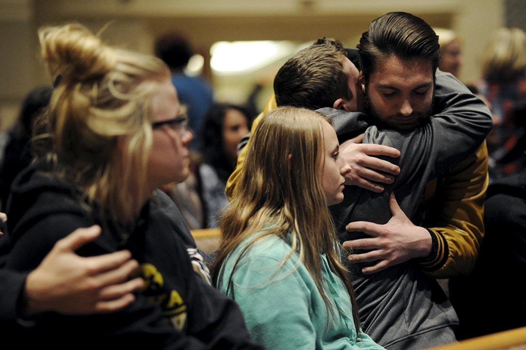 美國密歇根州發生嚴重槍擊案,受驚市民事後相擁互相安慰。攝:Mark Kauzlarich/ REUTERS