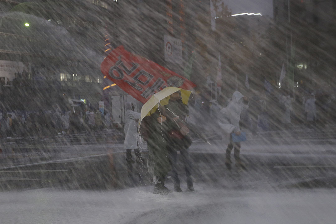 反政府示威者前往總統府途中舉傘,阻擋警方發射的催淚水劑。攝:Ahn Young-joon/AP