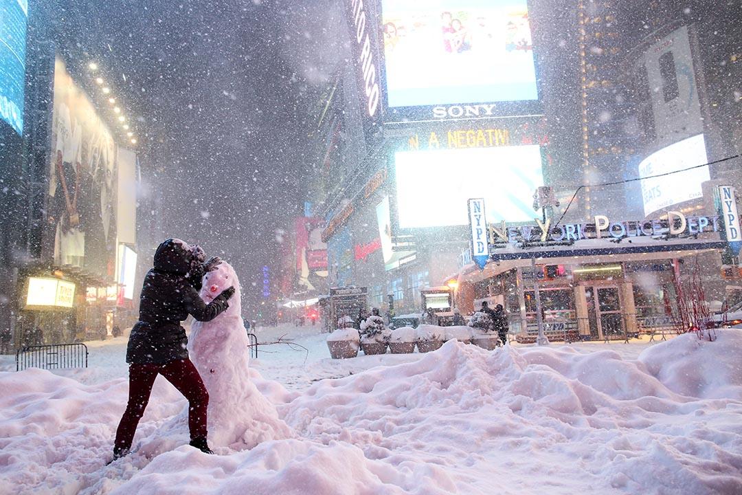 2016年1月23日,紐約時代廣場,一名女子在行車路上堆砌雪人。攝:Yana Paskova/Getty Images