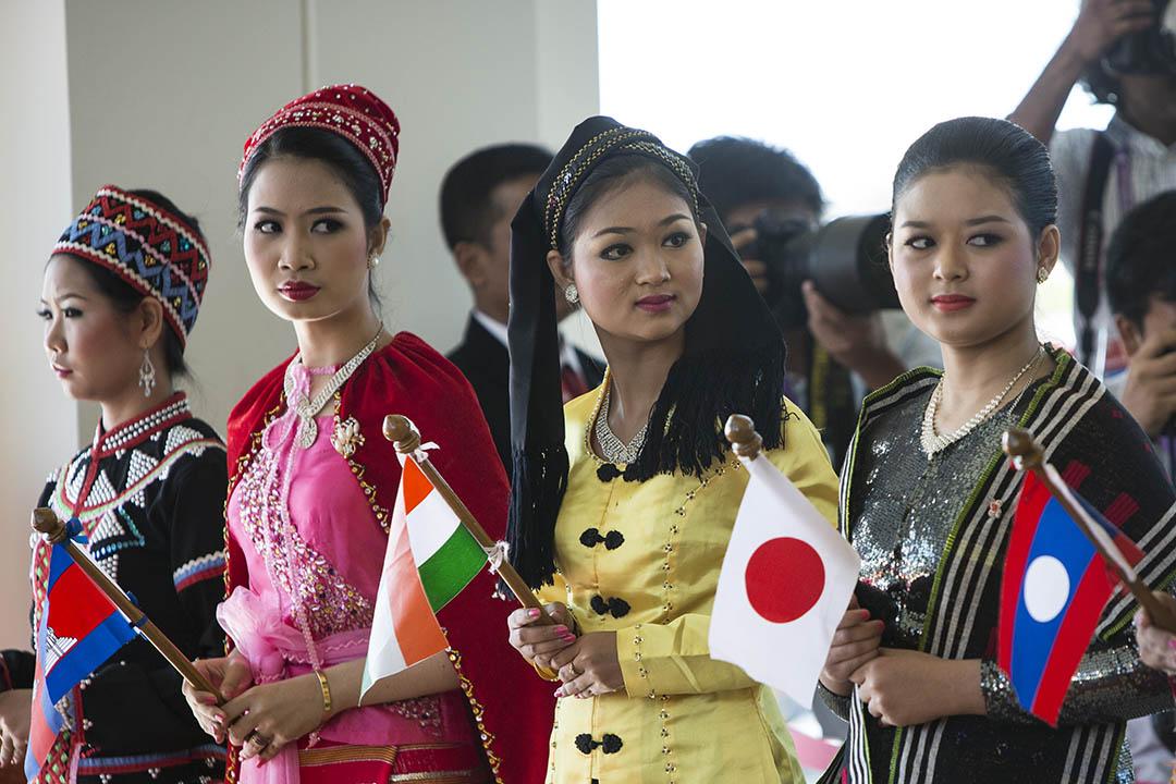 2015年11月13日,東協在緬甸舉行峰會,穿上傳統服飾的女士手持國旗在會上迎接各國元首。攝:Paula Bronstein/GETTY