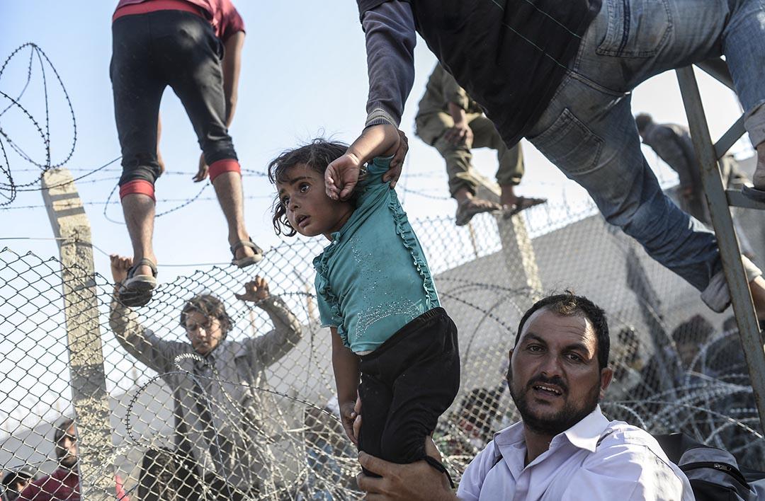 2015年6月14日,來自敘利亞的難民逃亡到土耳其,圖中的女童被難民抱起跨越鐵絲網,成功踏入土耳其國境。攝:BULENT KILIC/AFP