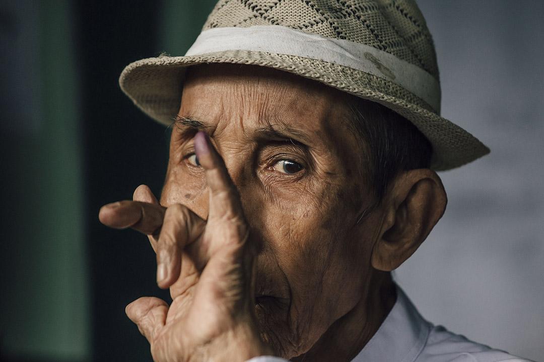 2015年11月8日,緬甸仰光BAHAN票站,一名男選民在投票後高舉染了紫色墨水的手指。政府為防止選民重覆投票,規定選民在投票後把一隻手指染上紫色墨水。攝:Anthony Kwan/端傳媒