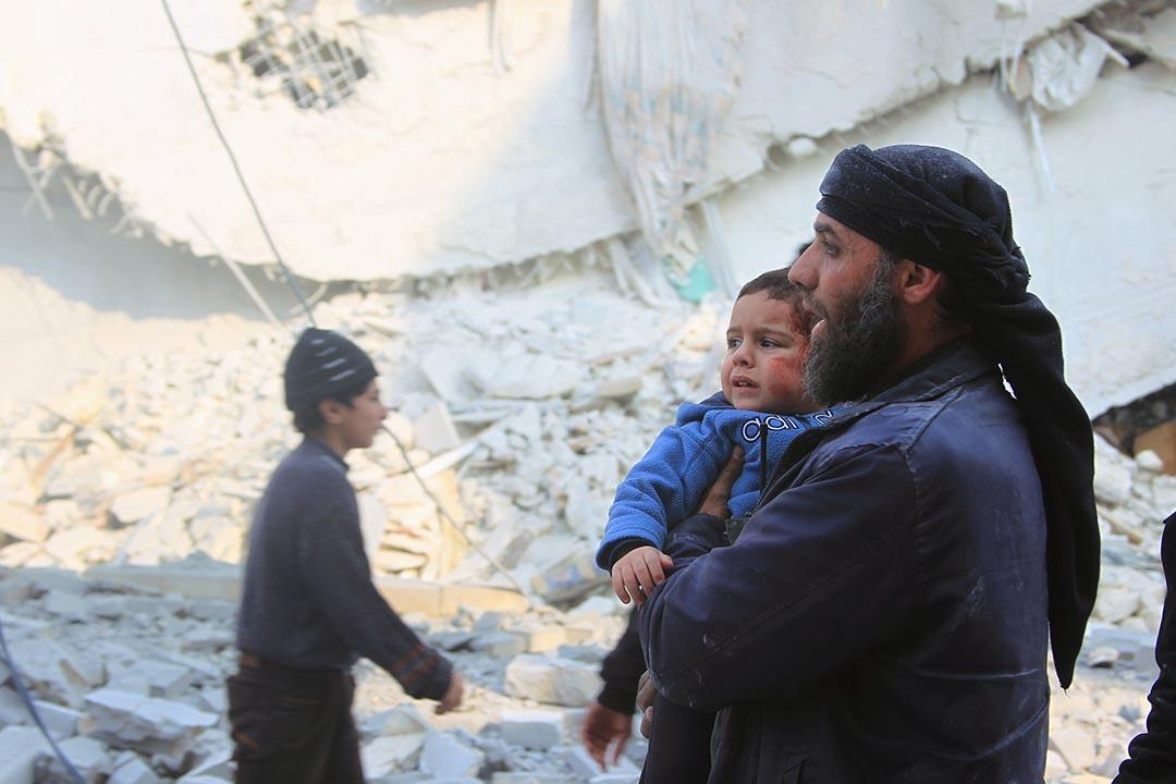 敘利亞救援人員抱住受傷的小孩離開空襲現場。攝 : Ammar Abdullah/REUTERS
