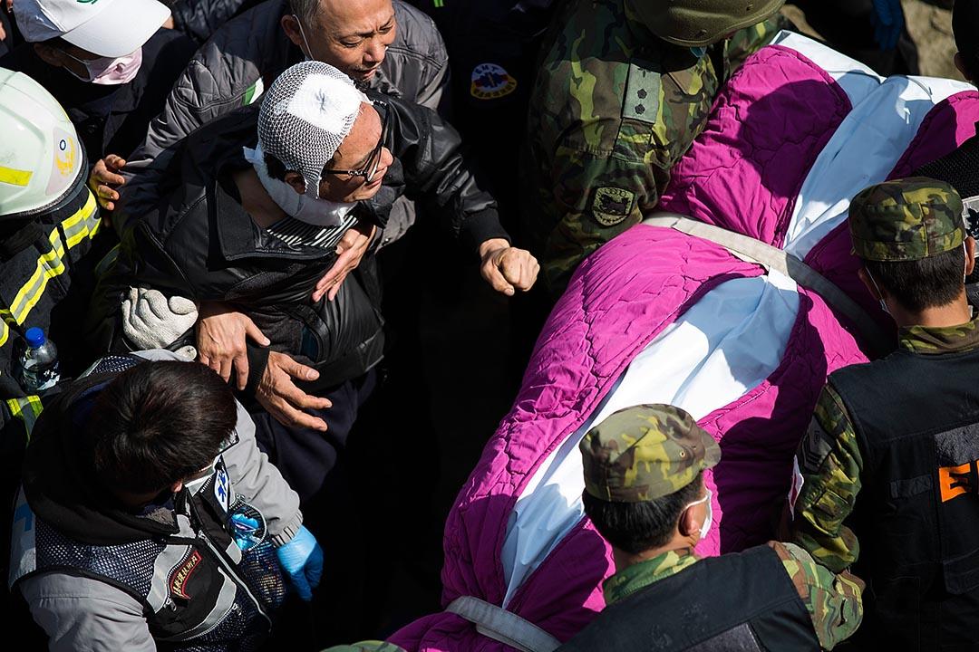 重建工程最難的部分,是對受災戶的心理救災。圖為頭部受創的災民,目睹救難人員抬出他母親的遺體。攝: Lam Yik Fei/Getty