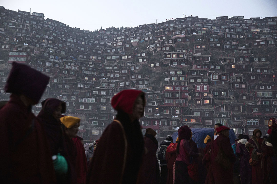 喇嘛和覺姆們離開佛學院,沿著黑暗的路回家。攝:Kevin Frayer/Getty Images