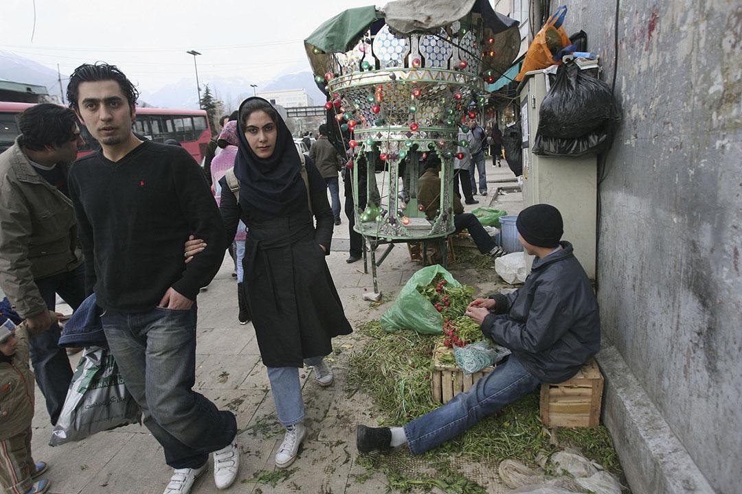 一對情侶在伊朗德克蘭逛街,路邊有擺檔的小販。攝:Majid Saeedi/GETTY
